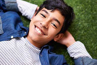 boy lying in grass smiling